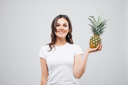 Young woman with pineapple on white background