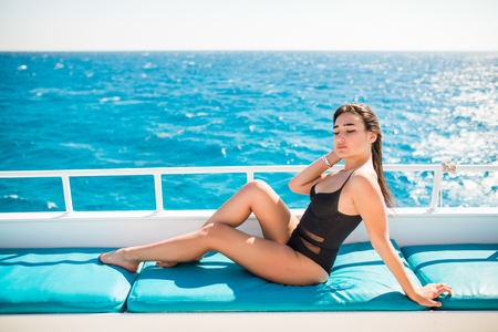 Beautiful woman smiling while lying on the deck of yacht
