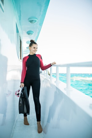 Young beautiful diver girl in black wetsuit standing on board of the yacht Stock Photo