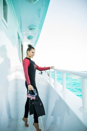 Young beautiful diver girl in black wetsuit standing on board of the yacht Banque d'images