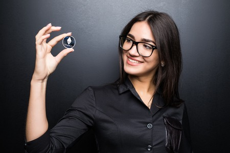 Business woman in glasses with Litecoin in hands isolated on black background. Stock Photo