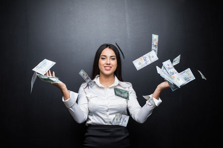 Happy business woman under a money rain made of dollars isolated on black background