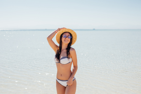 Happy woman on the beach in sunglasses and a straw hat on blue clear sea water