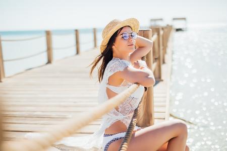 Beautiful woman in bikini on the wooden pier beside a water