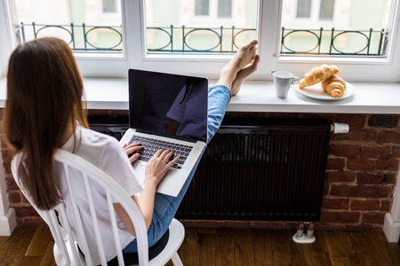 Young beauty woman check social networks in the morning before breakfast on windowsill