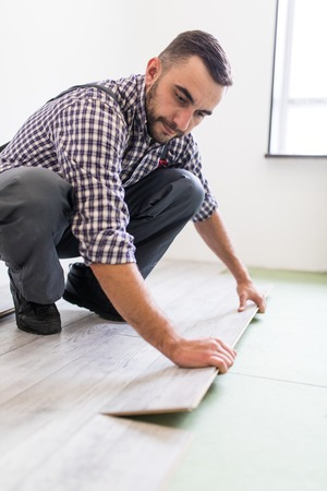 Man work laying laminate flooring at home Stock Photo