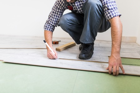 Close Up Man Hands Worker Installing Laminate Flooring In The
