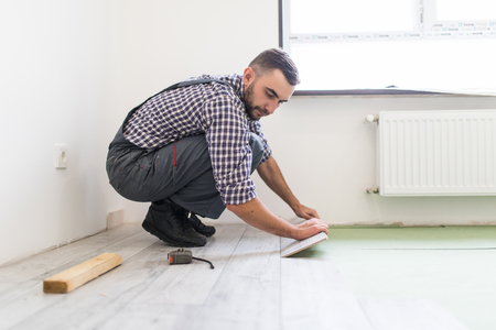 man is repairing the floor in the house, laminate flooring in the style of old boards Stock Photo