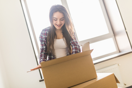 Woman packing and unpacking belongings in a carton box when moving home.