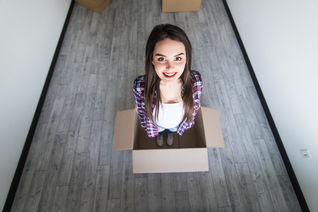 Woman sitting inside a cardboard box while packing Reklamní fotografie