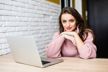 Young woman checking mail on laptop at home. Woman working on laptop at table at home Zdjęcie Seryjne