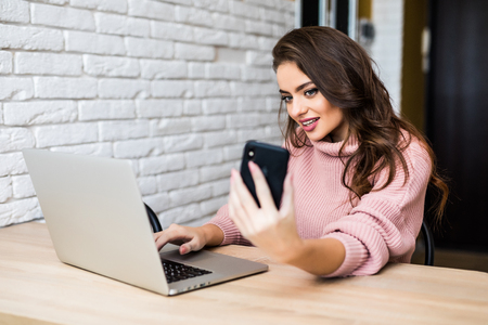 Beautiful girl in casual clothes is using a smart phone and a laptop, and smiling while sittingat table at home Zdjęcie Seryjne