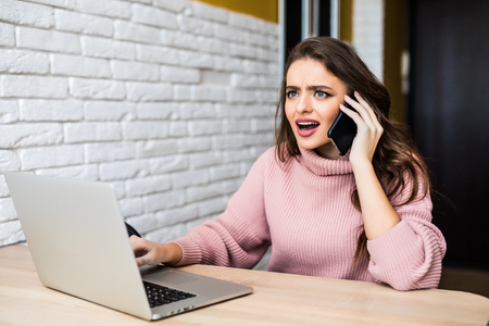 Angry student looking at a laptop and consulting on phone with customer service in her bedroom in a house interior Zdjęcie Seryjne