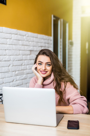 People, accounting, finances, family budget and financial issues concept. Serious young European woman calculating domestic expenses, sitting at dining table in front of open laptop computer Zdjęcie Seryjne