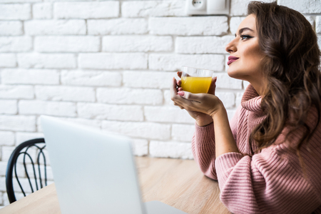 Woman drinking tea while on her laptop