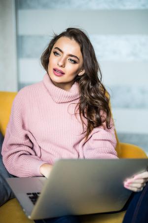 Caucasian woman using laptop computer for sending e-mail, sitting on sofa Zdjęcie Seryjne