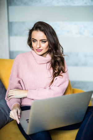 Casual woman using laptop in living room at home