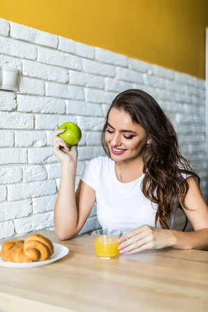 Young woman sitting at breakfast holding green apple, smiling at camera.