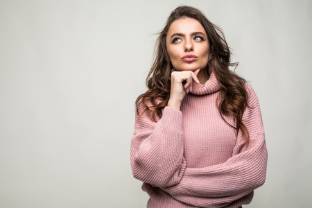 Young beautiful woman thinking looking to the side at blank copy space, isolated over white