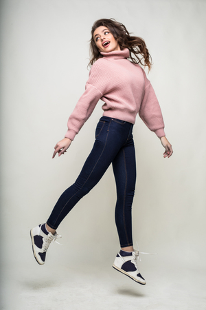 Full length portrait of a casual young woman jumping and looking at camera isolated over white Banco de Imagens