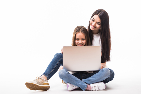 mother and child with laptop computer lying on the floor, isolated on white