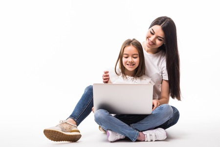 Mother and smile daughter watching on laptop screen sitting on floor on white Zdjęcie Seryjne