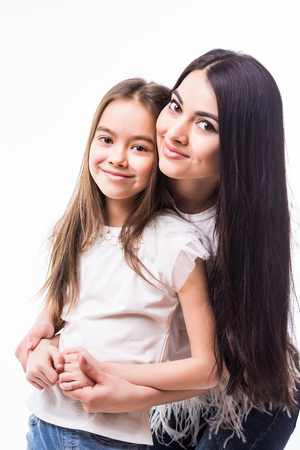 Close-up portrait of smiling mother hugging cute little daughter isolated on white