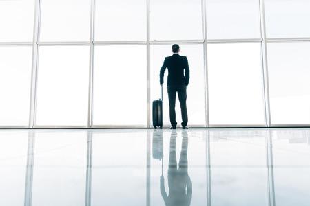 Arrière de l'homme d'affaires et valise à l'aéroport en attente de vol. Concept de voyage, valises voyageur dans le terminal de l'aéroport.