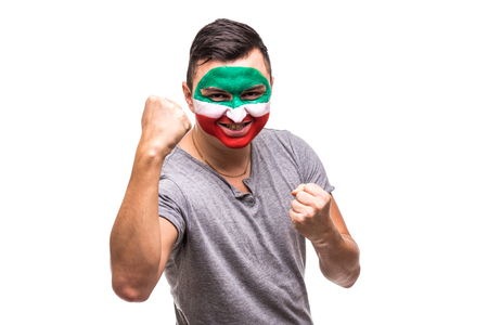 Handsome man supporter fan of Iran national team painted flag face get happy victory screaming into a camera. 版權商用圖片