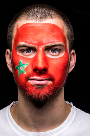 Portrait of handsome man face supporter fan of Morocco national team with painted flag face isolated on black background. 写真素材