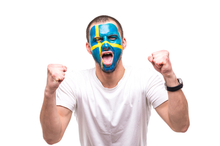 Handsome man supporter fan of Sweden national team with painted flag face get happy victory screaming into a camera.