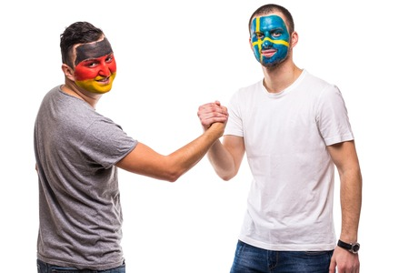 Handsome men supporters loyal fans of Sweden national team And Germany with painted flag face handshake on white.