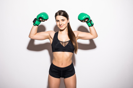 Smiling brunette fitness woman in boxing gloves showing her biceps over white background