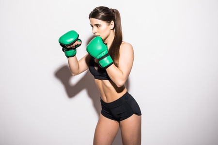 Beautiful Boxing Woman in green box gloves isolated on a white background