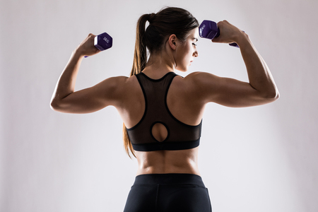 Back and hands of a young brunette sporty muscular woman working out with two metal dumbbells Stock Photo