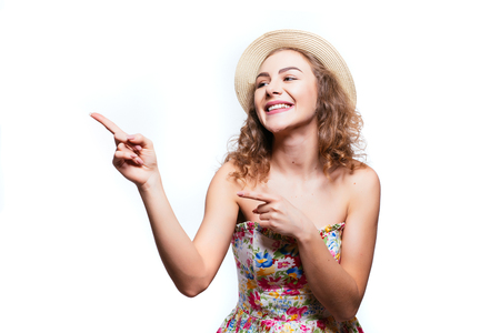 Portrait of an amazed cute girl in summer clothes pointing away at copy space with two fingers isolated Stock Photo