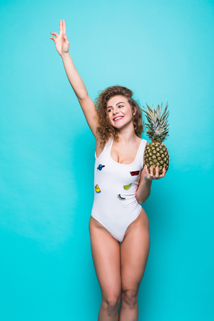 Portrait of young woman in swimsuit with pineapple on blue background. Standard-Bild