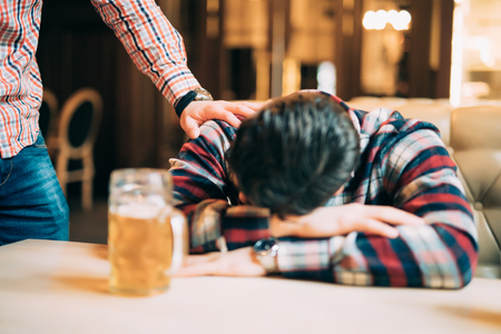 people, leisure, friendship and party concept - man with beer waking his drunk friend sleeping on table at bar or pub Foto de archivo