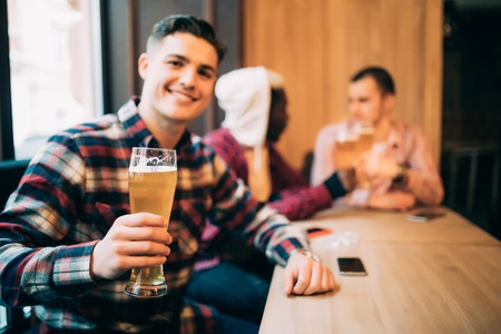 Man drink beer in front of two discussing drinking friends in pub. Imagens
