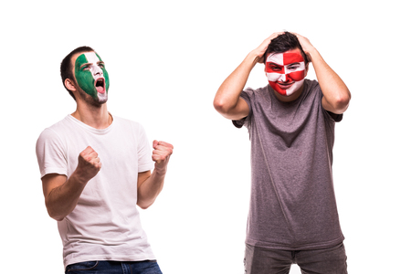 Happy Football fan of Nigeria celebrate win over upset football fan of Croatia with painted face isolated on white