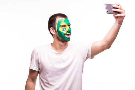 Fan support of Brazil national team take selfie on the phone with painted face isolated on white Stock Photo