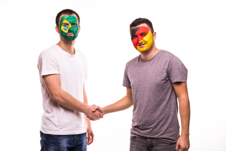 Football fans of Germany and Brazil national teams with painted face shake hands over white