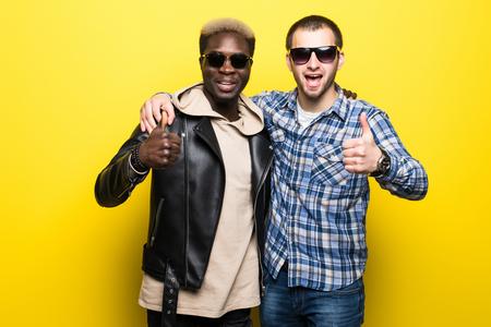 Joven mejor raza mixta mejores amigos hombres pulgares arriba aislado en amarillo Foto de archivo