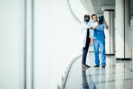 two male doctors reviewing x-ray in hospital corridor