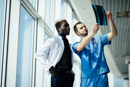 Concepto de salud, medicina y radiología: dos médicos mirando rayos x