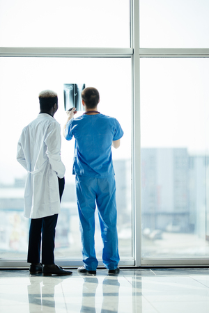 Back of two doctors checking X-rays on modern office background 版權商用圖片