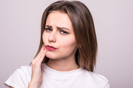 Teeth Problem. Woman Feeling Tooth Pain. Closeup Of A Beautiful Sad Girl Suffering From Strong Tooth Pain. Attractive Female Feeling Painful Toothache.