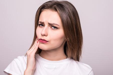Problema de los dientes. Mujer sintiendo dolor de dientes. Primer plano de una hermosa niña triste que sufre de dolor de dientes fuertes. Mujer atractiva sensación dolorosa dolor de muelas.