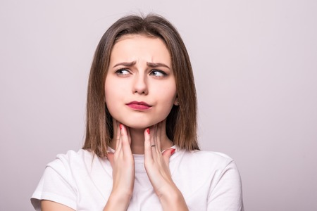 beautiful young woman has a sore throat, close-up, isolated on a gray Stock Photo