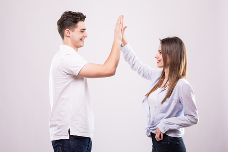 Joyful man and woman greeting each other with a high five isolated on white background 写真素材